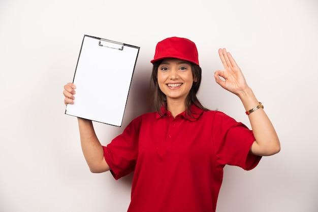Donna positiva in uniforme rossa con appunti vuoti