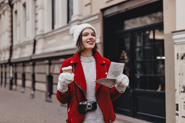 Positive woman in red warm jacket, cashmere sweater and white hat with gloves walks around city with coffee. tourist with retro camera around her neck holds map.
