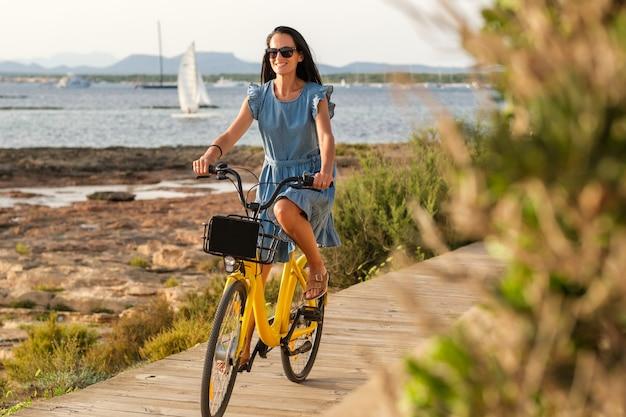 Positive woman riding bike along wooden promenade at seaside