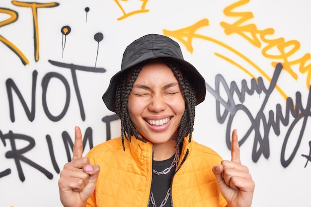 Positive woman smiles broadly points above with two index fingers has happy expression dressed in fashionable clothes poses against graffiti wall