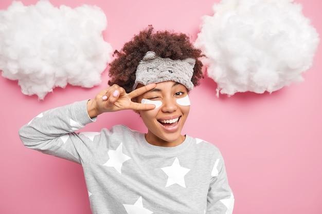 긍정적 인 여성의 미소는 기꺼이 눈을 통해 평화 제스처를 만듭니다 윙크 눈은 위의 분홍색 벽 흰 구름 위에 고립 된 파자마를 입은 눈 아래 콜라겐 패치를 적용합니다.