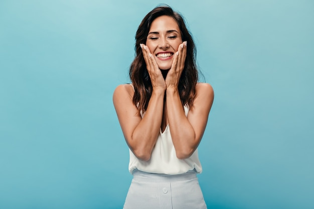 Positive woman smiling with eyes closed on blue background. dark-haired beautiful lady in light outfit rejoices and poses for camera.