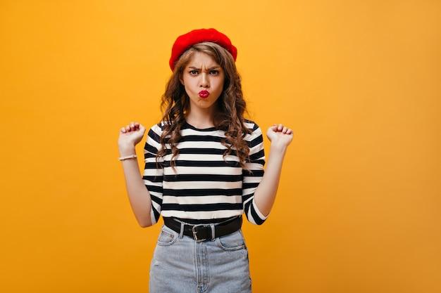 La donna positiva in camicia e berretto a strisce fa la faccia buffa. giovane signora riccia in gonna di jeans con ampia cintura nera in posa su sfondo isolato.