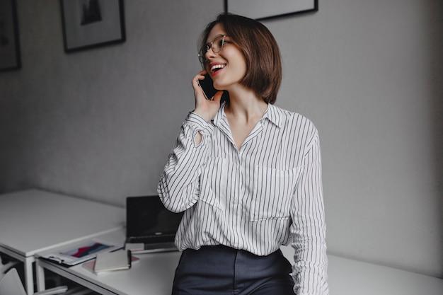 La donna positiva in camicia a righe si è appoggiata al tavolo bianco e parla al telefono su sfondo di laptop e forniture per ufficio.