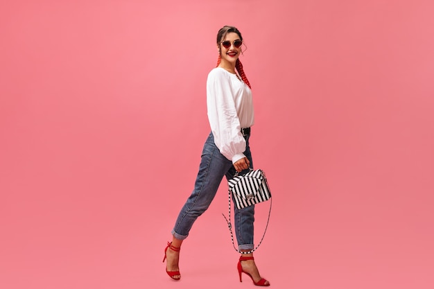 Positive woman in stylish outfit moves on pink background.  pretty woman in white blouse and red high heels is smiling at camera.
