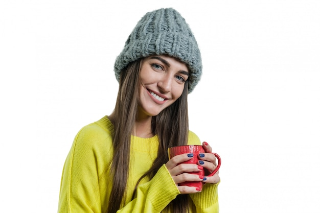 Positive woman in sweater, knitted hat with mug of hot drink