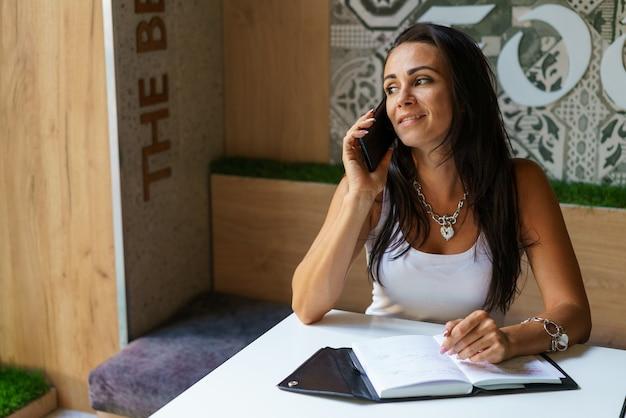 열린 노트북으로 카페에서 전화 통화를 하는 긍정적인 여자. 평상복을 입은 백인 소녀는 테이블에 앉아 있는 동안 전화로 의사소통을 한다