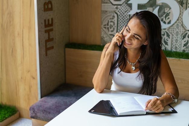 カジュアルな服装で開いたノートブック白人の女の子とカフェで電話で話しているポジティブな女性...