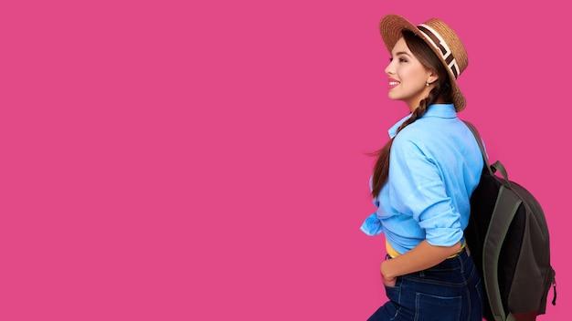 ピンクの孤立した背景にカジュアルな服、麦わら帽子、バックパックでポジティブな女性旅行者。若い笑顔の白人観光客