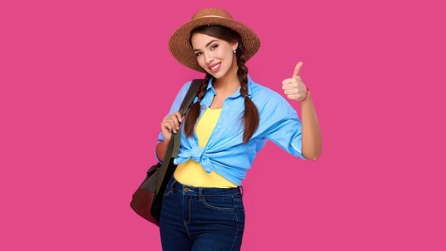 ピンクの孤立した背景に親指を立てるジェスチャーを示すカジュアルな服、麦わら帽子、バックパックのポジティブな女性旅行者。若い笑顔の白人観光客