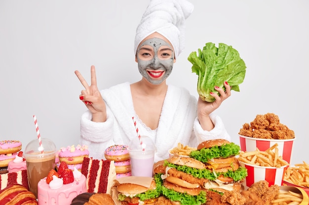 Positive woman undergoes beauty procedures at home makes peace gesture and holds green romaine lettuce
