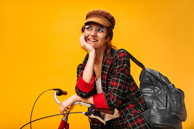 Positive woman in velvet cap and eyeglasses dreamily poses with bicycle