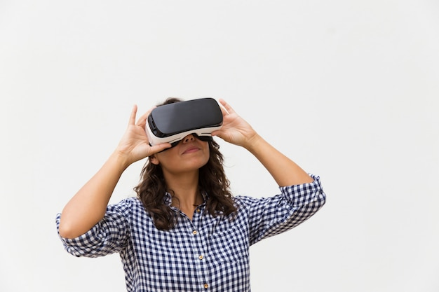 Positive woman wearing vr glasses, enjoying experience