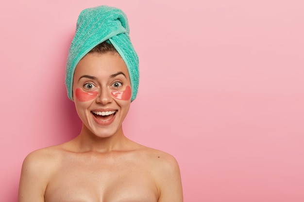 Positive woman wears collagen patches under eyes, has beauty treatments, stands naked indoor, has broad smile, appealing look