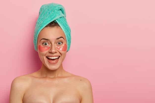긍정적 인 여성은 눈 밑에 콜라겐 패치를 착용하고, 미용 치료를 받고, 실내에서 알몸으로 서 있고, 넓은 미소를 지으며, 매력적인 모습을 보입니다.