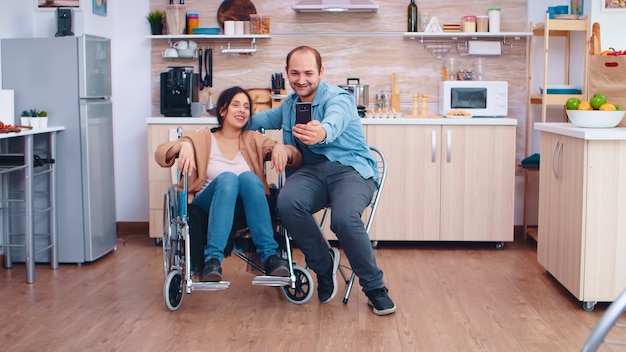 Positive woman in wheelchair and husband taking a selfie in kitchen using smartphone. hopeful husband with handicapped disabled disability invalid paralysis handicap person next to him, helping her to