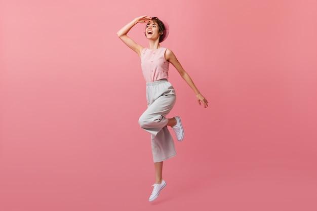 Donna positiva in scarpe bianche, saltando e guardando lontano