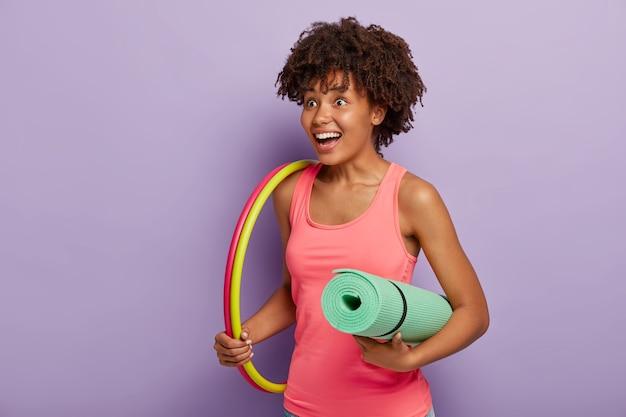 아프로 헤어 스타일을 가진 긍정적 인 여성, 롤업 피트니스 매트를 보유하고, 후프 운동을하고, 좋은 신체 모양을 원하며, 행복으로 어딘가에 보이는 건강한 라이프 스타일이 스포츠 장비를 보유하고 있습니다.
