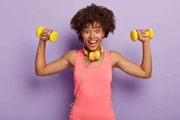 アフロヘアカットのポジティブな女性、ダンベルで腕を上げ、黄色のヘッドフォンとピンクのベストを着て、紫色のスタジオの壁にポーズをとる