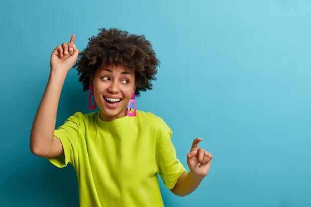 La donna positiva con l'acconciatura afro balla con le braccia alzate, si sente spensierata e ottimista, estremamente felice ed esprime gioia, indossa una maglietta verde, isolata sul muro blu, si muove energicamente
