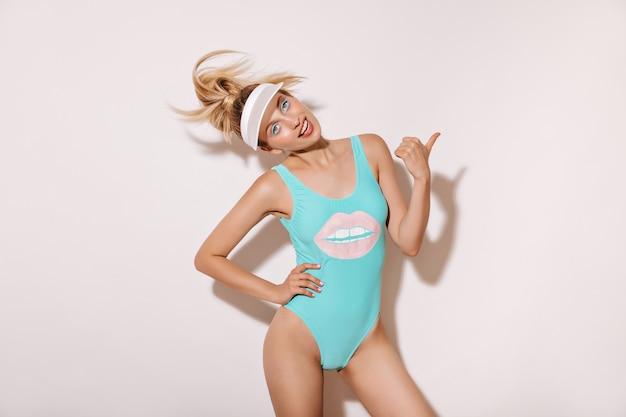 금발 머리와 파란색 멋진 수영복과 모자에 유행 메이크업을 가진 긍정적 인 여자 웃고 흰 벽에 텍스트를위한 장소를 가리키는