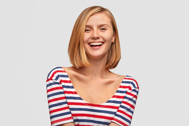 Positive woman with broad smile, shows white teeth, laughs at good joke, likes funny story from interlocutor, has slim body, dressed in striped jacket