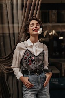 Positiva donna con capelli castani in camicetta con pizzo e jeans pone con fiore in bocca all'interno. donna dai capelli ondulati con labbra rosse sorride nella caffetteria.