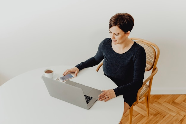 Positive woman with a cup of tea telecommuting