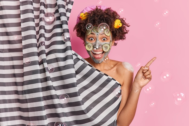 Positive woman with curly hair applies clay mask for skin rejuvenation poses against pink wall soap bubbles around. look at this hygiene product