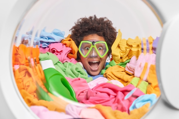 Positive woman with curly hair wears snorkeling mask stuck in laundry poses at washing machine drum being greatly surprised by something