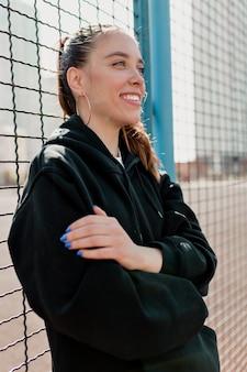 Позитивная женщина с темной прической в темном наряде улыбается и веселится в городе в солнечный теплый день