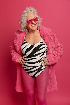 Positive woman with gray hair, smiles broadly, keeps hands on waist, keeps fit and healthy, wears trendy sunglasses, swimsuit, pink tights and robe, dreams about vacation during self isolation