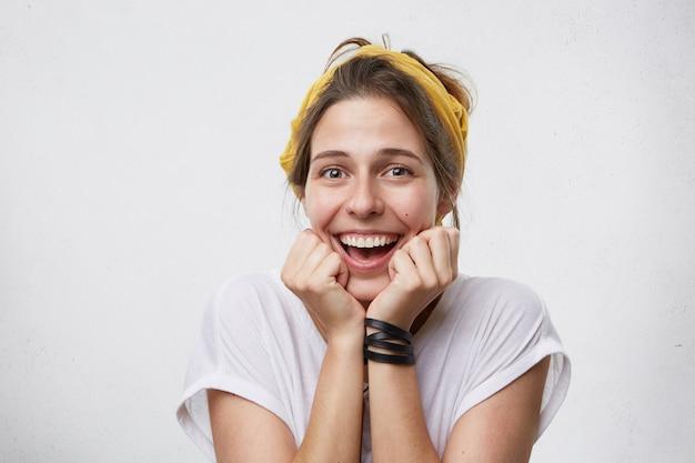 Позитивная женщина со счастливым выражением лица позирует на фоне белой бетонной стены