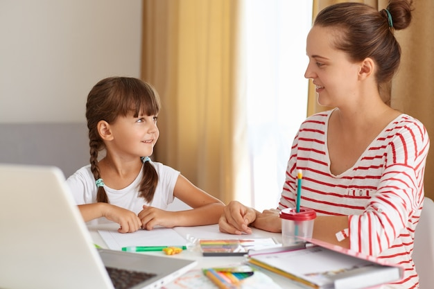Positive woman with her female kid posing in living room at table, mother helping daughter with lessons, explaining new rule, online distance education.