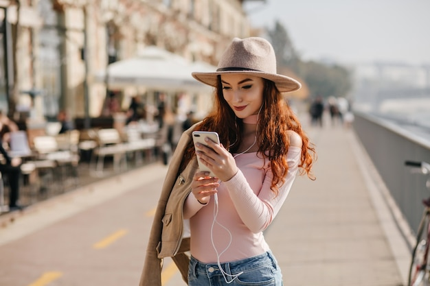 Позитивная женщина с длинной прической с помощью смартфона, стоя на набережной
