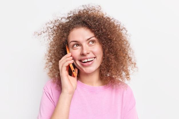 Позитивная женщина с натуральными вьющимися волосами зовет друга на встречу, держит смартфон возле уха, смотрит вверх, радостно наслаждается забавным разговором, носит повседневную розовую футболку, изолированную над белой стеной