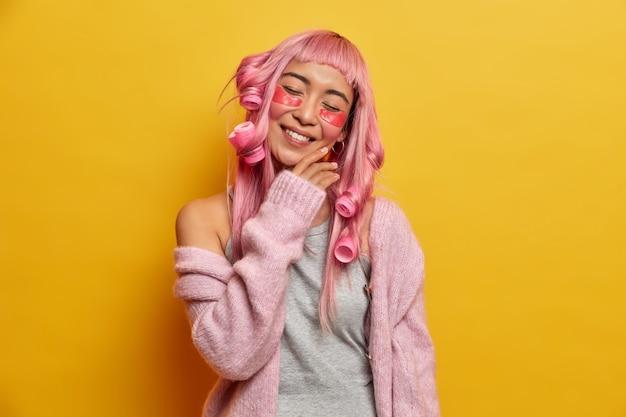 Donna positiva con capelli rosei, inclina la testa, tocca delicatamente il viso, gode di una pelle morbida, ha un sorriso a trentadue denti, fa acconciatura, si prende cura della pelle sotto gli occhi