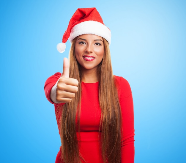 Positive woman with santa hat on blue background