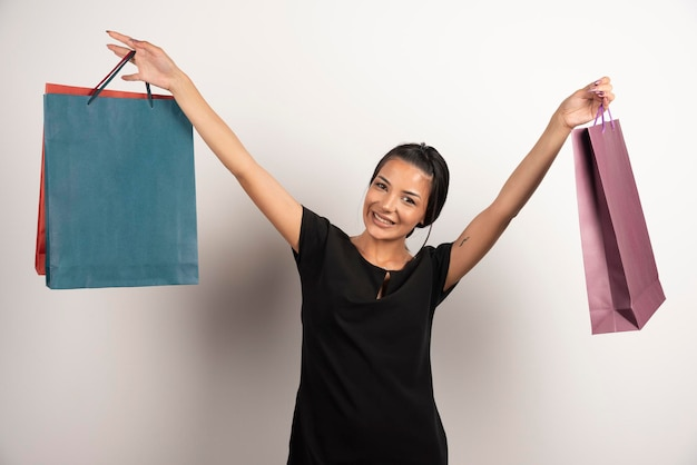 Positive woman with shopping bags posing on white wall.