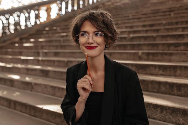 Donna positiva con capelli corti e labbra luminose in vetri che sorridono all'esterno. signora alla moda in abiti neri in posa sulle scale.