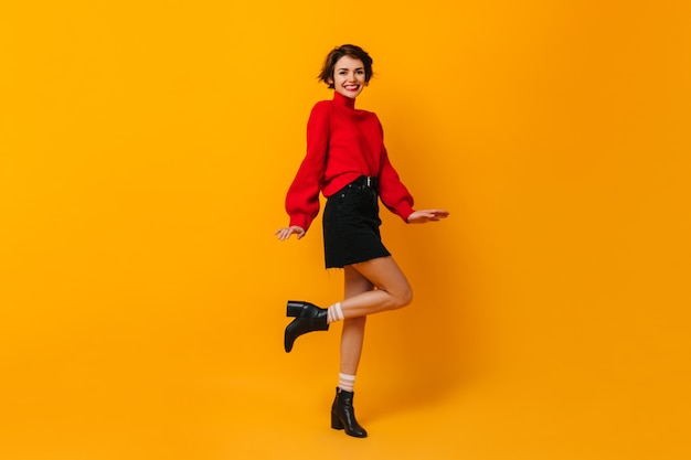 Positive woman with short hair dancing on yellow wall
