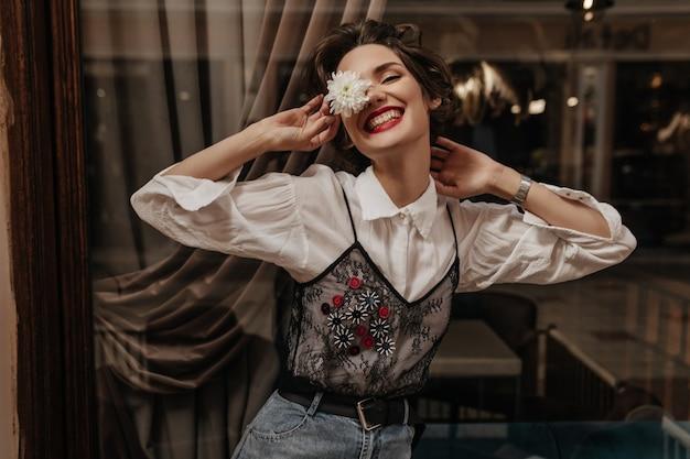 긴 소매 흰색과 검은 색 셔츠에 짧은 머리를 가진 긍정적 인 여성이 카페에서 진심으로 웃고 있습니다. 안에 꽃을 들고 청바지에 쾌활 한 아가씨입니다.