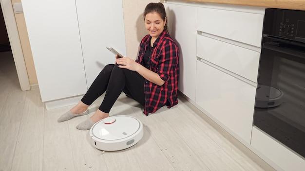 スマートフォンを持ったポジティブな女性が床に座って、自宅のキッチンで木の床から汚れを取り除く現代のロボット掃除機を見ています