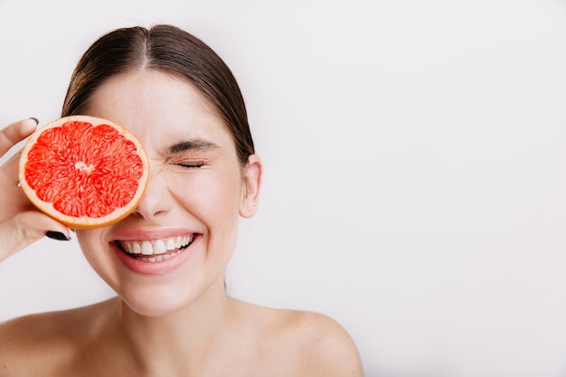 Positive woman with smile closed her eyes. girl with healthy skin is posing with grapefruit on isolated wall.
