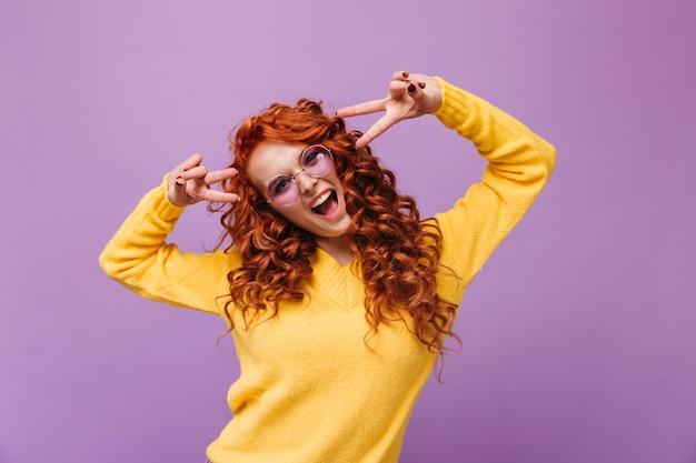 La donna positiva in maglione giallo e occhiali mostra un segno di pace e ride sul muro lilla