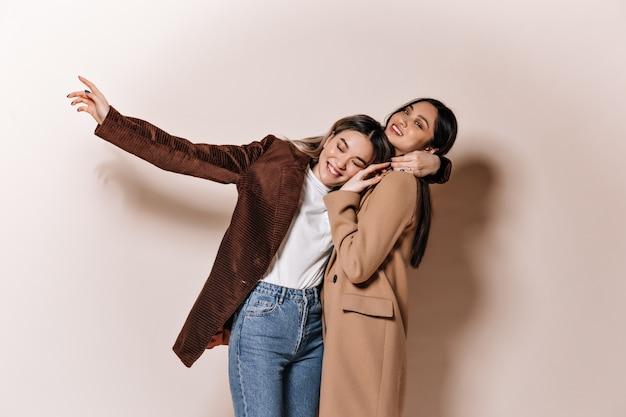 갈색 의상을 입은 긍정적 인 여성은 베이지 색 벽에 재미를 느낍니다.