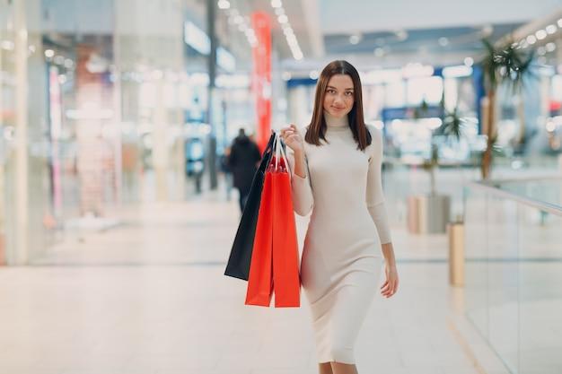 종이 쇼핑백을 손에 들고 긍정적인 젊은 성인 여성