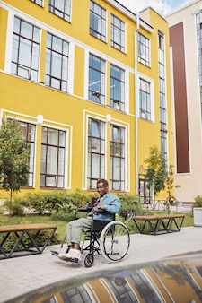 Positive young african-american man with paralyzed legs sitting in wheelchair and recording audio message on phone against sanatorium building