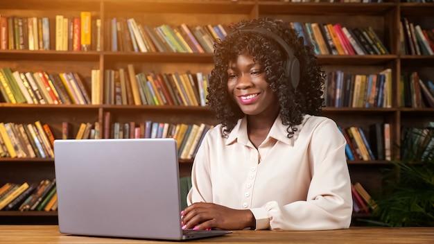 긍정적인 젊은 아프리카계 미국인 여성은 집 검역소 책장 근처의 나무 테이블에 앉아 있는 현대적인 노트북을 통해 화상 통화를 합니다.