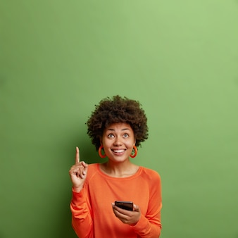 Positive young afro american woman holds modern smartphone indicates upwards with index finger demonstrates copy space for your advertisement isolated over green wall